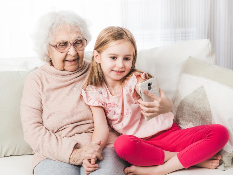 Enkelin, die selfie mit Urgroßmutter nimmt lizenzfreie stockfotos