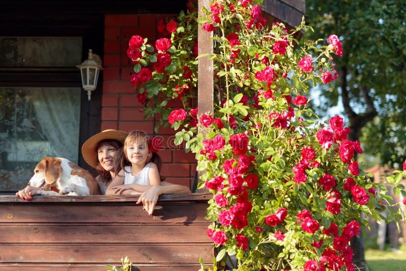 Enkelin, Großmutter und ihr Hund auf der Veranda des Dorfhauses lizenzfreie stockfotos