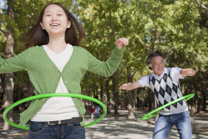 Enkelin mit dem Großvater, der Spaß hat und mit Plastikband im Park spielt stockbild