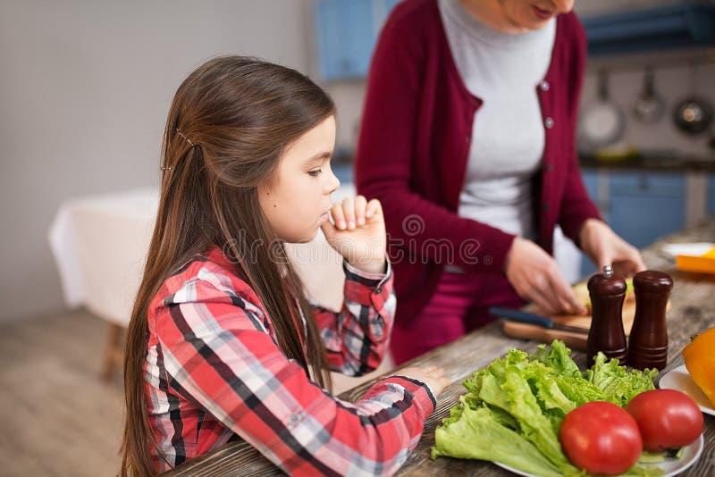 Enkelin mit mischendem Salat der Großmutter in der Küche lizenzfreie stockbilder
