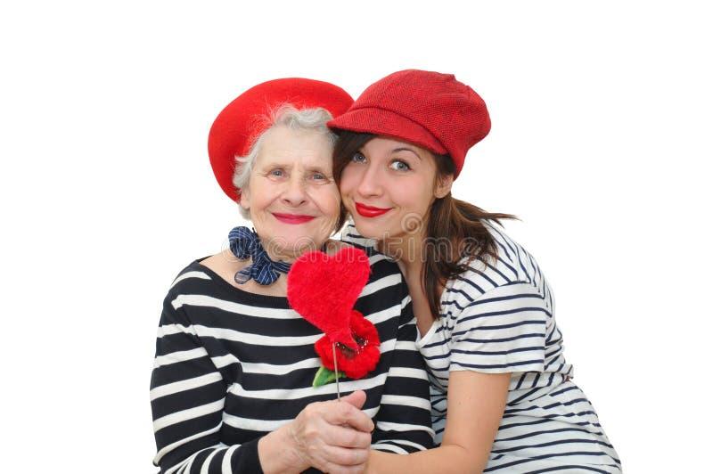 Enkelin und Großmutter mit rotem Herzen lizenzfreie stockfotos