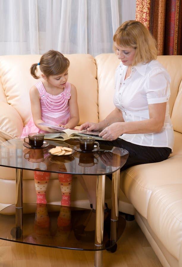 Enkelkind und Großmutter lasen Buch lizenzfreie stockbilder
