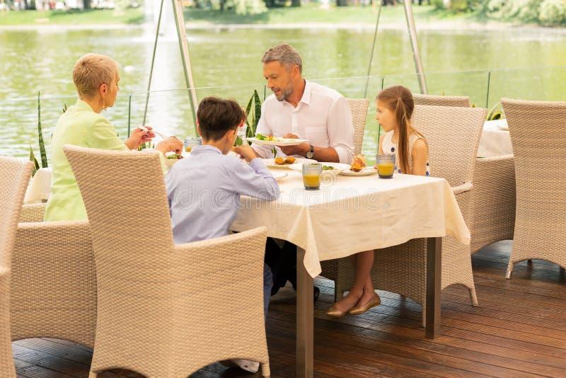 Enkelkinder, die Frühstück nahe See mit Großeltern genießen lizenzfreies stockfoto