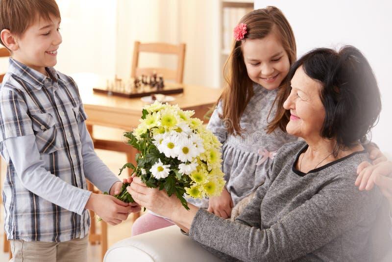Enkelkinder, die ihrer Großmutter einen Blumenstrauß geben stockbilder