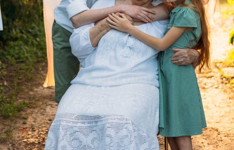 Enkelkinder, Kinder, die Großmutter, ältere Frau umarmen Sitzungsgroßmutter und -enkelkinder Großmutter umfasst Enkelkind lizenzfreie stockbilder