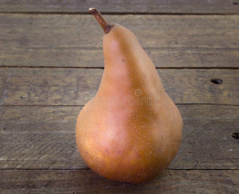 Enkelt Bosc päron på den lantliga wood tabellen arkivfoton