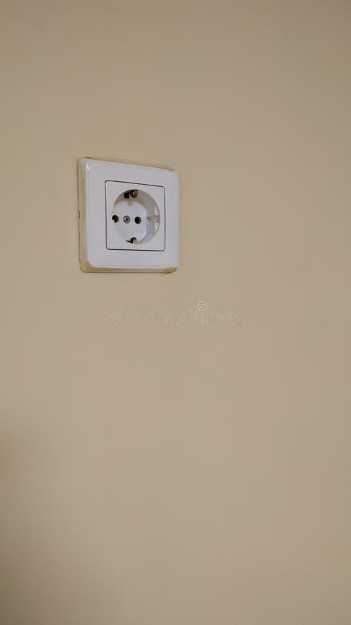 Enkelt elektriskt uttag på väggen som målas i beige färg N?rbild royaltyfri foto