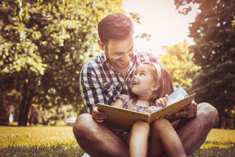 Enkelt fadersammanträde på gräs med den lilla dottern royaltyfri bild