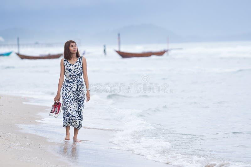 Enkelt gå för kvinna som är ensamt med sorgframsidan på havsstranden arkivfoton