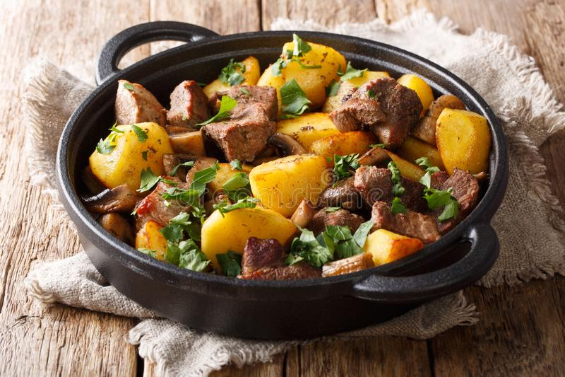 Enkelt hurtigt mål av stekte potatisar med grisköttkött och champinjonnärbild i en panna horisontal royaltyfri fotografi