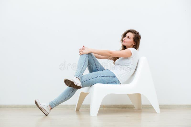 Enkelt kvinnasammanträde på vit stol arkivbild