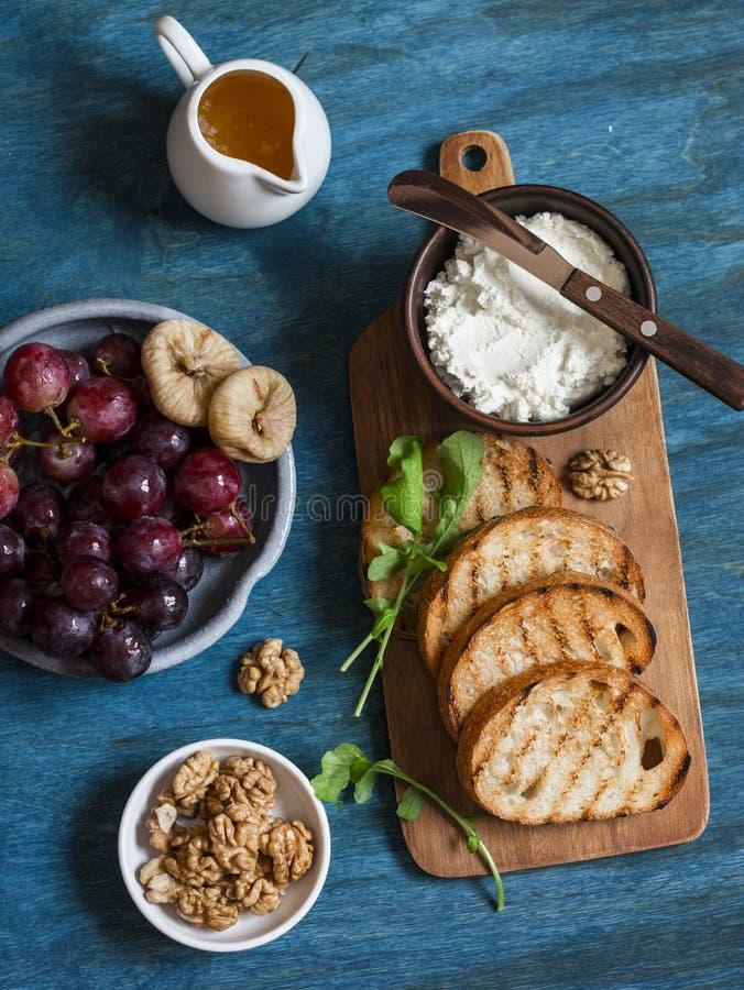 Enkelt mellanmål - getost, grillat bröd, druvor, torra fikonträd, valnötter, honung På träbakgrund royaltyfri foto