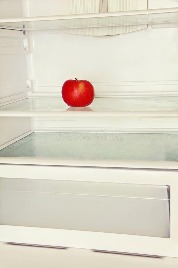 Enkelt rött äpple i inhemskt kylskåp royaltyfria foton