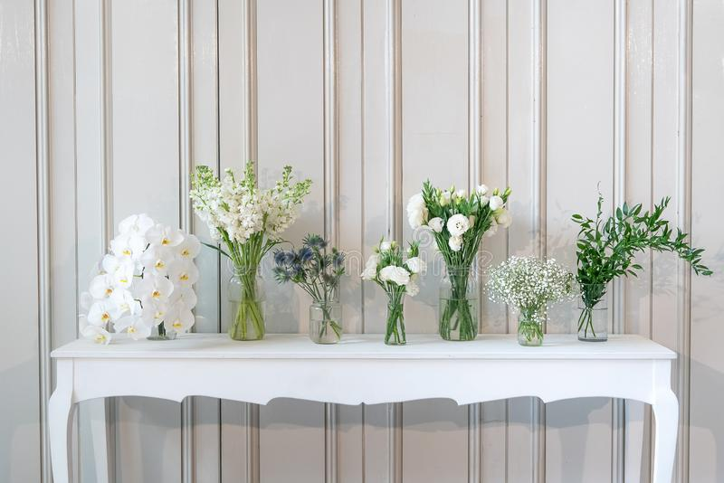 Enkelt sammansättning av den olika vita blomman i vas på den vita tappningtabellen royaltyfria foton