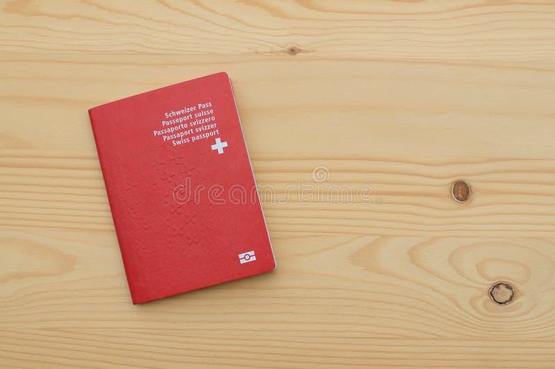 Enkelt schweiziskt pass på en trätabell royaltyfri fotografi