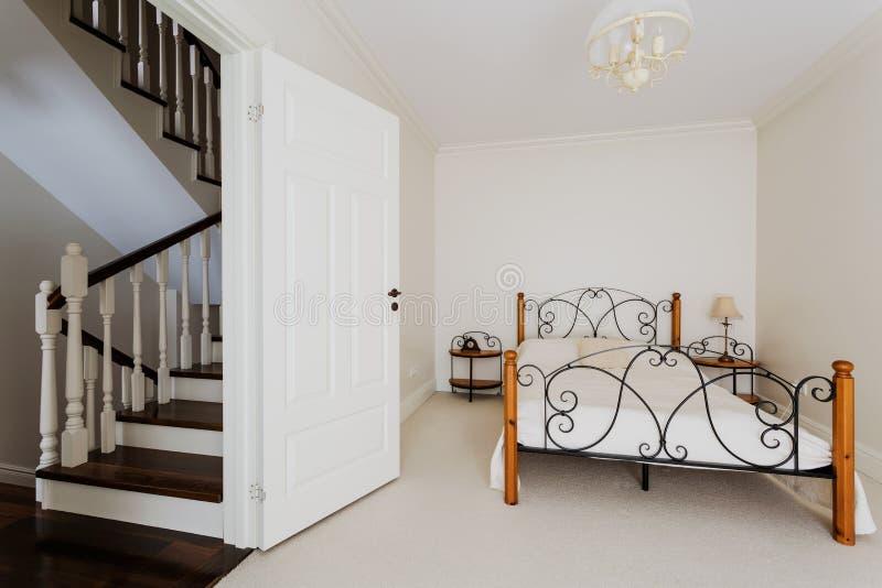 Enkelt sovrum och trätrappa arkivbild