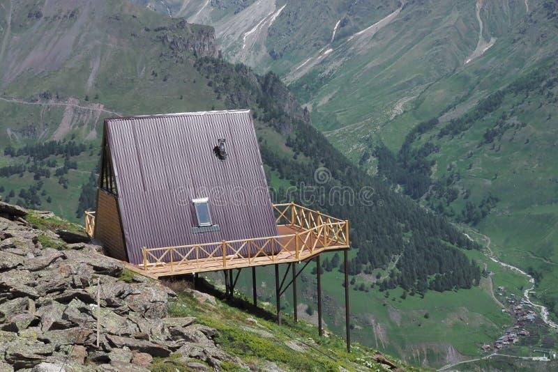 Enkelt trähus med ett rött tak på en kullehöjdpunkt i bergen med en härlig sikt av den gröna dalen på en solig dag arkivbilder