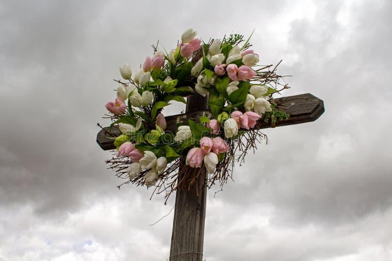 Enkelt träkors med en krans av vita och rosa siden- tulpan royaltyfri foto