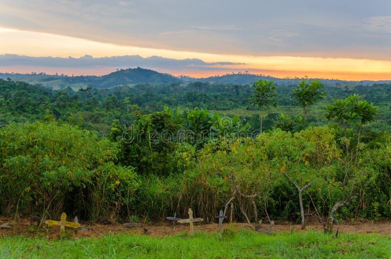Enkla träkors och gravar framme av den frodiga djungeln och den dramatiska solnedgången i Kongofloden arkivbild