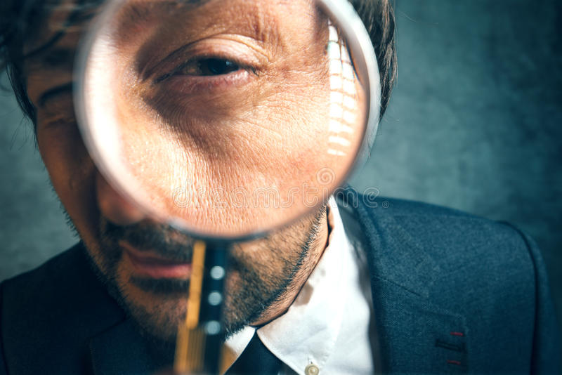 Enlarged eye of tax inspector looking through magnifying glass. Inspecting offshore company financial papers, documents and reports royalty free stock photography