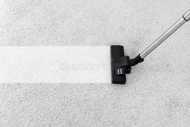 Enlever la saleté du tapis mou avec l'aspirateur images stock
