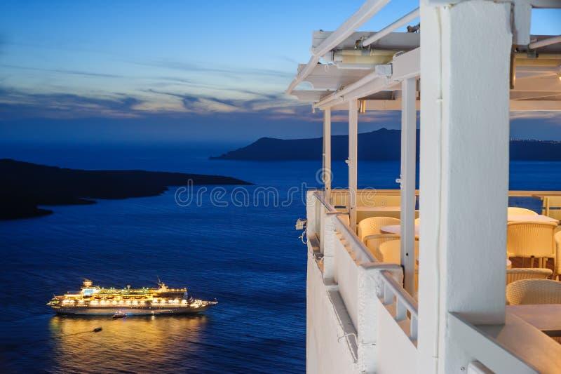 Enlighted在日落以后的游轮在圣托里尼海岛的,希腊Fira镇附近 库存图片