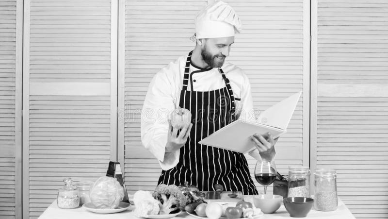 Enligt recept Sk?ggig kock f?r man som lagar mat mat Grabben l?ste bokrecept Begrepp f?r kulinariska konster Mannen l?r recept royaltyfri bild