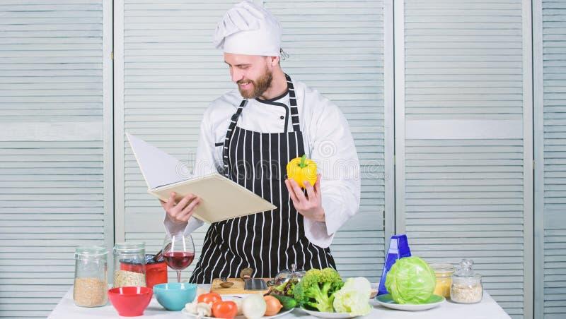 Enligt recept Sk?ggig kock f?r man som lagar mat mat Grabben l?ste bokrecept Begrepp f?r kulinariska konster Mannen l?r recept royaltyfria bilder