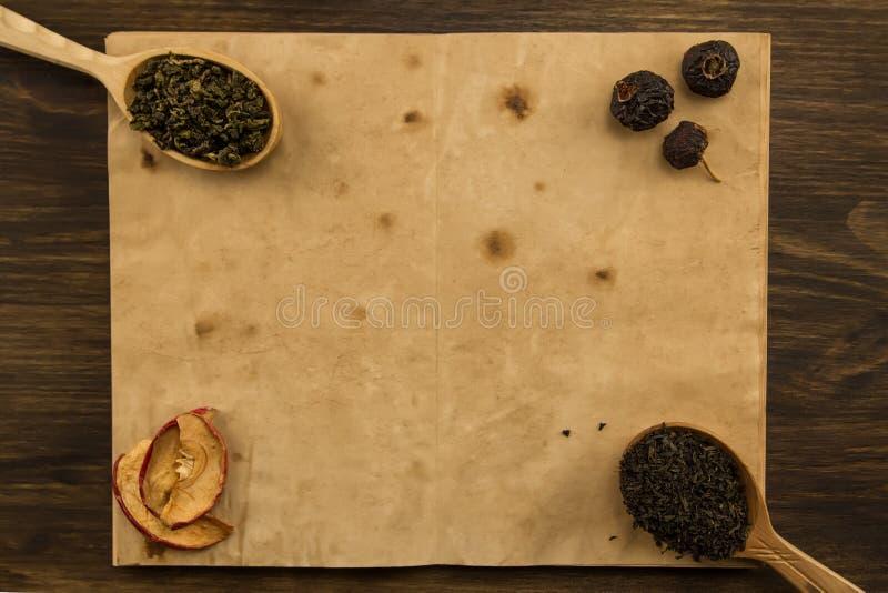 Ennegrézcase, Oolong en una cuchara, las manzanas secadas en el viejo espacio en blanco abren el libro en fondo de madera Menú, r imagenes de archivo