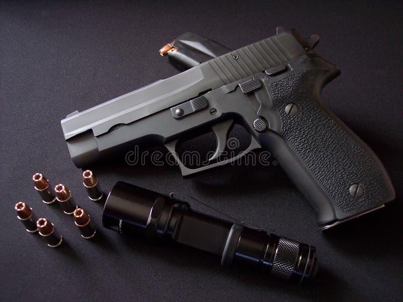 Ennegrezca la arma de mano de la pistola semiautomática de 9m m con la munición y la linterna fotografía de archivo