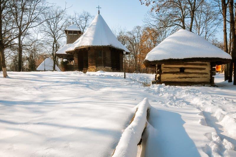 Enneigement dans un village roumain avec une vieille église en bois photos libres de droits