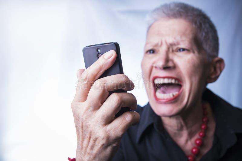 Enojado mayor en su teléfono celular fotografía de archivo