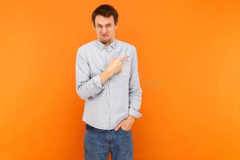 Enoje al hombre que señala el finger en el espacio de la copia y que mira la cámara foto de archivo