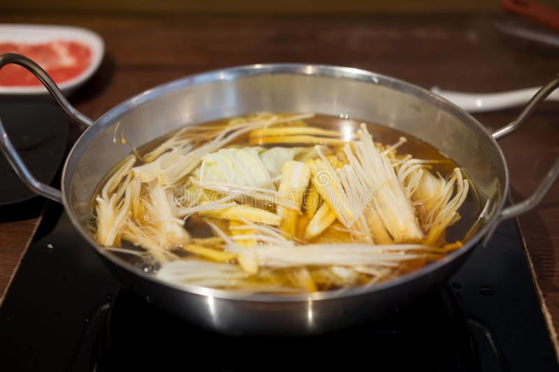 Enoki mushroom and baby corn in a hot pot royalty free stock image