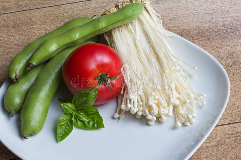 Enokitake Mushrooms, edamame beansEdamame, basilico and tomato. Enoki mushrooms, edamame beans, tomato and leafs of basilico on the white plate stock image