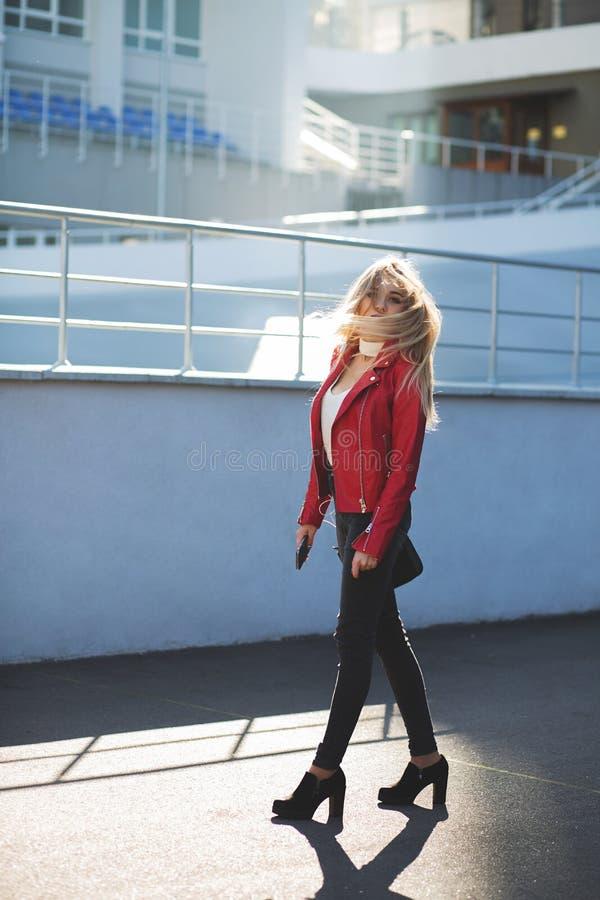 Enorm blond flicka som bär det röda omslaget som går ner gatan med att fladdra hår royaltyfri bild