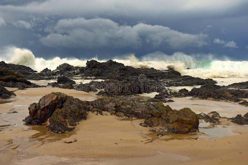 Enorm brytande bränning nära stenig shoreline royaltyfri bild