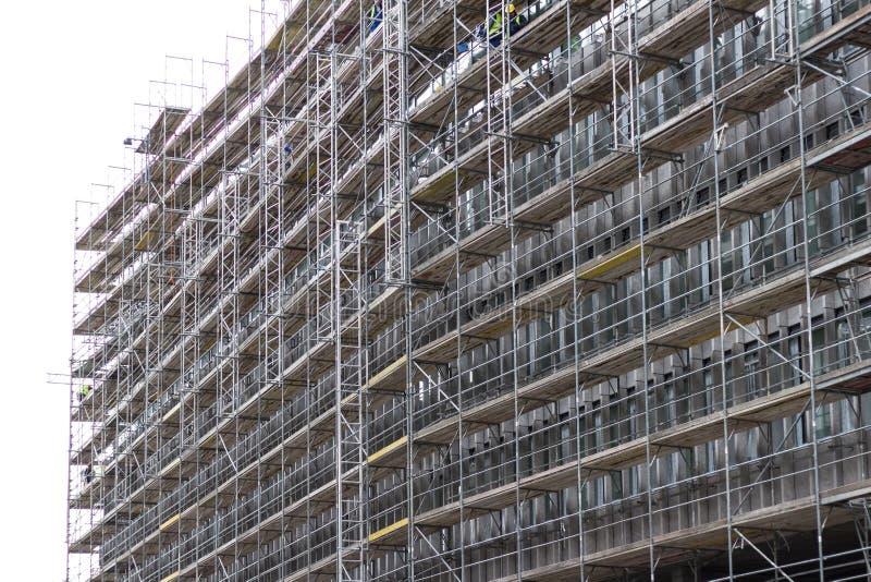 Enorm byggnadsfasad med materialet till byggnadsställning, konstruktionsplats arkivbilder