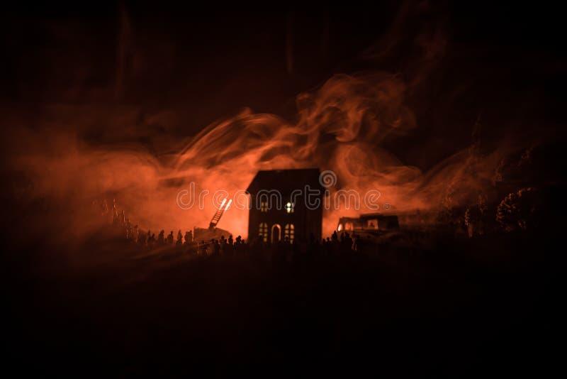 Enorm flamma som distraherar huset på brand Brandmotor med stegen och brandman som försöker att spara huset Brandman på arbete Br royaltyfri bild