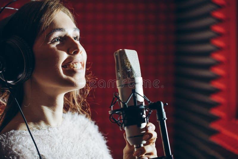 Enorm flicka som tycker om sjunga sången i studion royaltyfri fotografi
