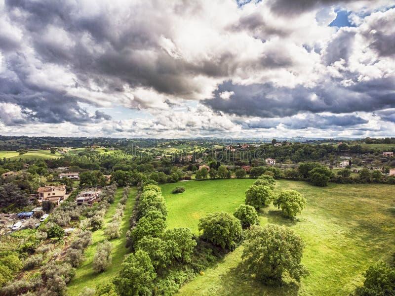 Enorm flyg- sikt med gröna kullar, fält som planteras med fruktträd, och ängar och scenisk himmel royaltyfri fotografi