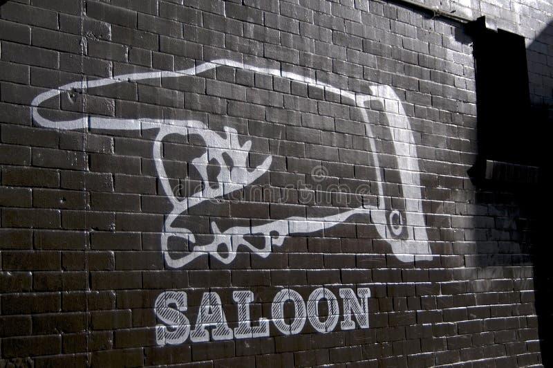 Enorm hand som målas på en svart vägg med texten 'salong 'in under royaltyfri foto