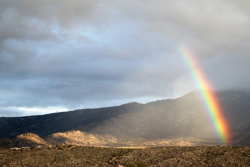 Enorm himmel mycket av moln med den mycket lilla regnbågen över de Santa Catalina bergen i Tucson, Arizona royaltyfri foto