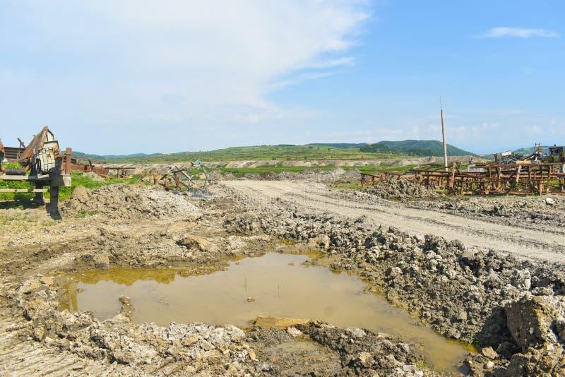 Enorm kolgruva för öppen grop som göras med stora grävskopor, laddare, lastbilar och staplande maskiner Tunga industriella maskin royaltyfri fotografi