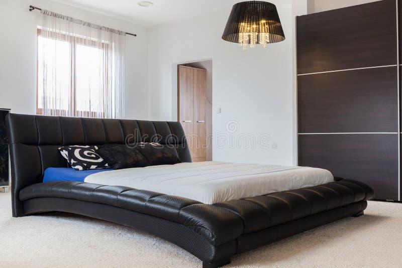 Enorm lädersäng i sovrum royaltyfri bild