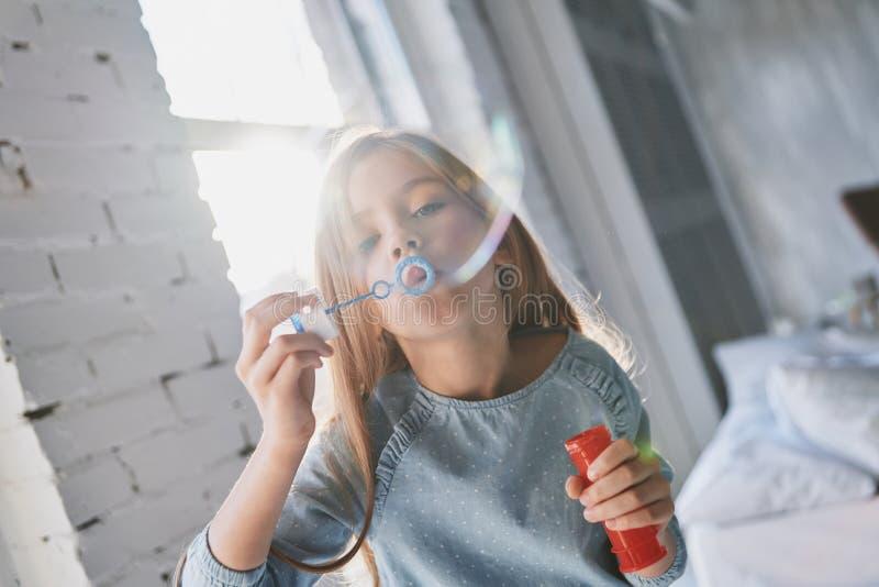 So enorm! Nettes kleines Mädchen, das eine Seifenblase bei der Ausgabe von t durchbrennt stockbilder