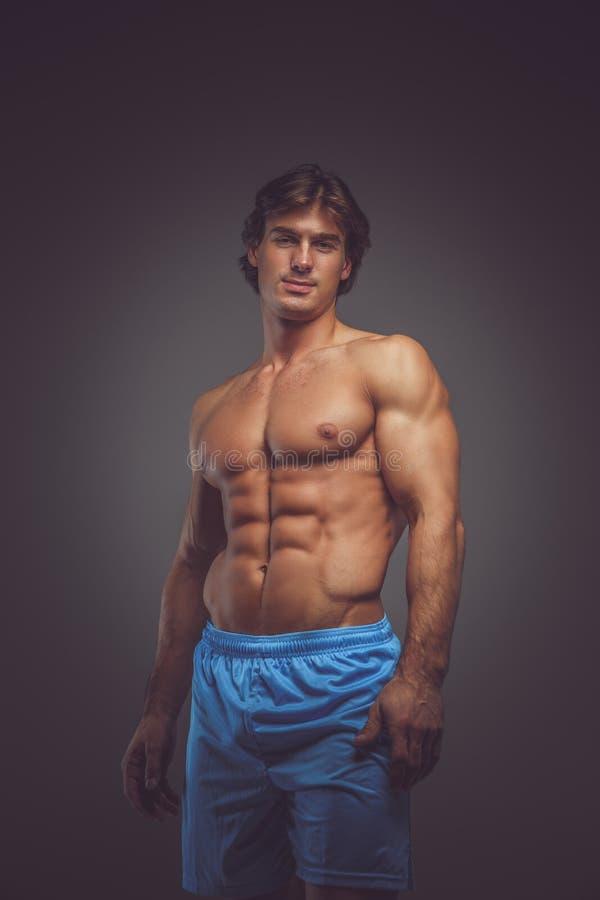 Enorm shirtless kroppsbyggare i blåa kortslutningar royaltyfri foto