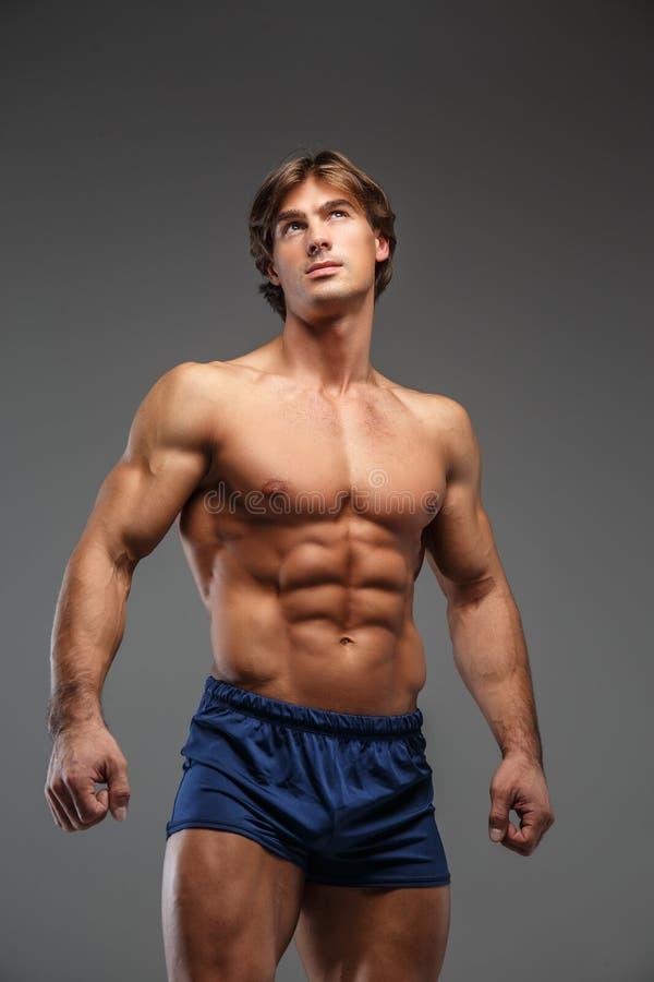 Enorm shirtless kroppsbyggare i blåa kortslutningar royaltyfri fotografi