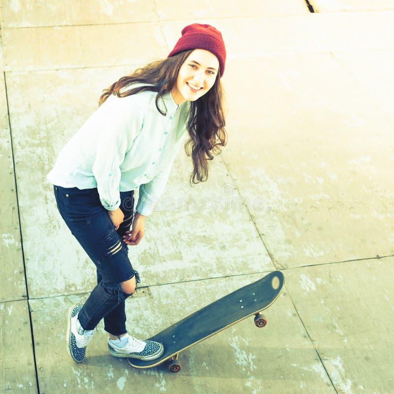 Enorm skateboarderflicka med skateboarden som är utomhus- på skatepark royaltyfri fotografi