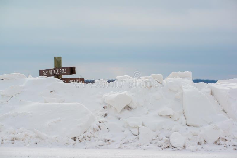 Enorm snöig bank från den plogade lantliga vägen med den lantliga teckenstolpen som knappt är synlig ovanför insnöat området för  arkivfoto